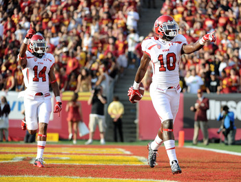 LOS ANGELES, CA - SEPTEMBER 10:  DeVonte Christopher #10 of the Utah Utes celebrates his touchdown with Reggie Dunn #14 to trail 10-7 turnover the USC Trojans during the second quarter at Los Angeles Memorial Coliseum on September 10, 2011 in Los Angeles,