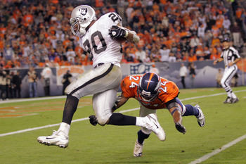 DENVER, CO - SEPTEMBER 12:   Darren McFadden #20 of the Oakland Raiders is tackled by Champ Bailey #24 of the Denver Broncos at the one yard line after rushing for 47 yards to set up a fourth quarter touchdown at Sports Authority Field at Mile High on Sep
