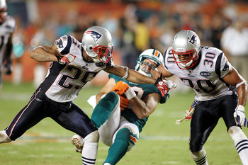 MIAMI GARDENS, FL - SEPTEMBER 12:  Tight end Anthony Fasano #80 of the Miami Dolphins is brought down by Safety's Patrick Chung #25 and Josh Barrett #30  of the New England Patriots at Sun Life Stadium on September 12, 2011 in Miami Gardens, Florida.  (Ph