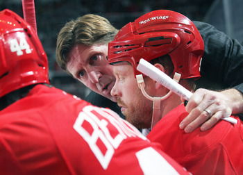 DETROIT,MI - DECEMBER 10:  Head coach Mike Babcock of the Detroit Red Wings gives instructions to Johan Franzen #93 and team during the game against the Montreal Canadiens at the Joe Louis Arena on December 10, 2010 in Detroit, Michigan. The Wings defeate
