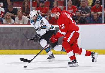 DETROIT - MAY 10: Pavel Datsyuk #13 of the Detroit Red Wings controls the puck in front of Patrick Marleau #12 of the San Jose Sharks during the first period in Game Six of the Western Conference Semifinals during the 2011 NHL Stanley Cup Playoffs on May
