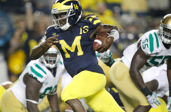 ANN ARBOR, MI - SEPTEMBER 10: Denard Robinson #16 of the Michigan Wolverines looks for yards on a fourth quarter run while playing the Notre Dame Fighting Irish at Michigan Stadium on September 10, 2010 in Ann Arbor, Michigan. Michigan won the game 35-31.