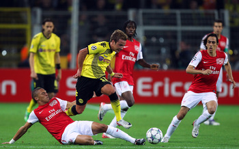 DORTMUND, GERMANY - SEPTEMBER 13:  Kieran Gibbs (L) of Arsenal tries to tackle Mario Gotze (C) of Borussia Dortmund next to Yossi Benayoun of Arsenal during the UEFA Champions League Group F match between Borussia Dortmund and Arsenal FC at Signal Iduna P
