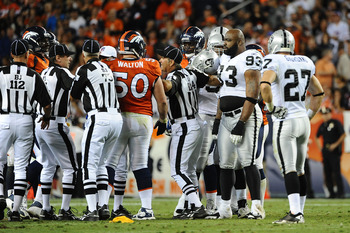 DENVER, CO - SEPTEMBER 12:  Umpire Carl Paganelli #124 seperates J.D. Walton #50 of the Denver Broncos and Tommy Kelly #93 of the Oakland Raiders during the game at Sports Authority Field at Mile High on September 12, 2011 in Denver, Colorado.  (Photo by