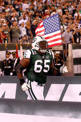 EAST RUTHERFORD, NJ - SEPTEMBER 11:  Brandon Moore #65 of the New York Jets runs with an American Flag on to the field during pregame festivities against the Dallas Cowboys during their NFL Season Opening Game at MetLife Stadium on September 11, 2011 in E