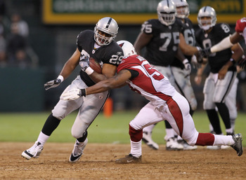 OAKLAND, CA - AUGUST 11:  Michael Bush #29 of the Oakland Raiders is tackled by Daryl Washington #58 of the Arizona Cardinals at O.co Coliseum on August 11, 2011 in Oakland, California.  (Photo by Ezra Shaw/Getty Images)