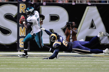 ST. LOUIS, MO - SEPTEMBER 11: Michael Vick #7 of the Philadelphia Eagles scrambles as Chris Long #91 of the St. Louis Rams dives for him at the Edward Jones Dome on September 11, 2011 in St. Louis, Missouri. The Eagles defeated the Rams 31-15. (Photo by J