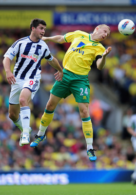 NORWICH, ENGLAND - SEPTEMBER 11:  Shane Long of West Bromwich Albion battles with Richie De Laet of Norwich during the Barclays Premiership match between Norwich City and West Bromwich Albion at Carrow Road on September 11, 2011 in Norwich, England.  (Pho