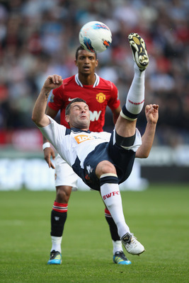 BOLTON, ENGLAND - SEPTEMBER 10:  Paul Robinson of  Bolton Wanderers clears from Nani of Manchester United during the Barclays Premier League at the Reebok Stadium on September 10, 2011 in Bolton, England.  (Photo by Michael Steele/Getty Images)