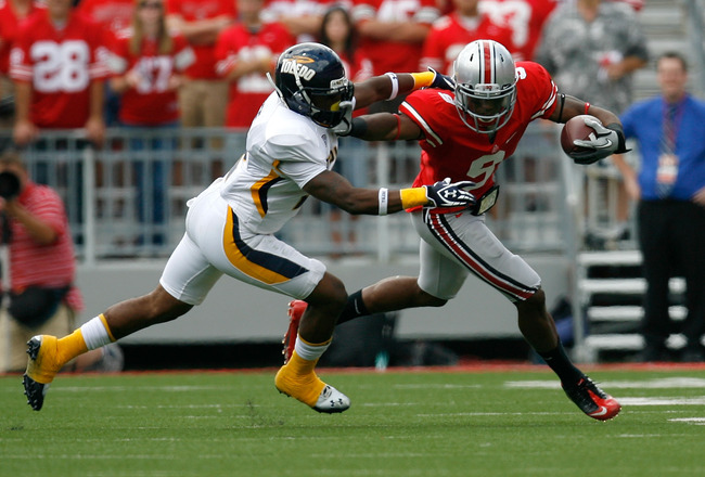 COLUMBUS, OH - SEPTEMBER 10:  Verlon Reed #9 of the Ohio State Buckeyes stiff-arms Taikwon Paige #2 of the Toledo Rockets on September 10, 2011 at Ohio Stadium in Columbus, Ohio. (Photo by Kirk Irwin/Getty Images)