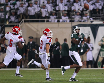 EAST LANSING, MI - SEPTEMBER 02:  B.J. Cunningham #3 of the Michigan State Spartans catches the ball against Donald D'Alesio #8 and Jeremy Edwards #5 of the Youngstown State Penguins during an NCAA football game at Spartan Stadium on September 2, 2011 in
