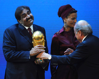 ZURICH, SWITZERLAND - DECEMBER 02: The Emir State of Qatar HH Sheikh Hamad bin Khalifa Al-Thani is presented with the World Cup Trophy by FIFA President Joseph S Blatter as Sheikha Mozah bint Nasser Al Missned looks on during the FIFA World Cup 2018 & 202