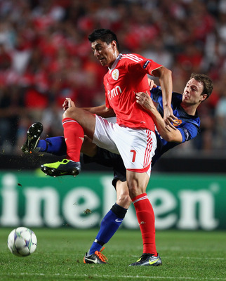 LISBON, PORTUGAL - SEPTEMBER 14:  Jonny Evans of Manchester United challenges Oscar Cardozo of SL Benfica during the UEFA Champions League Group C match between SL Benfica and Manchester United at the Estadio da Luz on September 14, 2011 in Lisbon, Portug