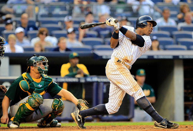 NEW YORK, NY - AUGUST 25: Curtis Granderson #14 of the New York Yankees hits a grand slam home run in the 8th inning in front of catcher Anthony Recker of the Oakland Athletics at Yankee Stadium on August 25, 2011 at Yankee Stadium in the Bronx borough of