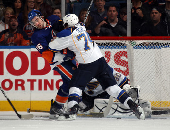 UNIONDALE, NY - MARCH 05: Matt Moulson #26 of the New York Islanders is hit by T.J. Oshie #74 of the St. Louis Blues at the Nassau Coliseum on March 5, 2011 in Uniondale, New York. The Islanders defeated the Blues 5-2. (Photo by Bruce Bennett/Getty Images