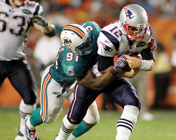 MIAMI GARDENS, FL - SEPTEMBER 12:  Quarterback Tom Brady #12 of the New England Patriots is sacked by Defensive End Cameron Wake #91 of the Miami Dolphins at Sun Life Stadium on September 12, 2011 in Miami Gardens, Florida.  (Photo by Marc Serota/Getty Im