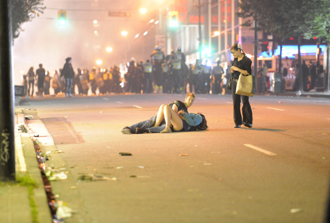 VANCOUVER, BC - JUNE 15:  (EDITORS NOTE: Image is uncropped. Photo five of five, in sequence.) A couple lies on a street as an unidentified woman approaches on June 15, 2011 in Vancouver, Canada. Vancouver broke out in riots after their hockey team the Va