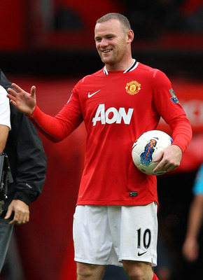MANCHESTER, ENGLAND - AUGUST 28:  Wayne Rooney of Manchester United carries the match ball after scoring a hat trick in the Barclays Premier League match between Manchester United and Arsenal at Old Trafford on August 28, 2011 in Manchester, England.  (Ph