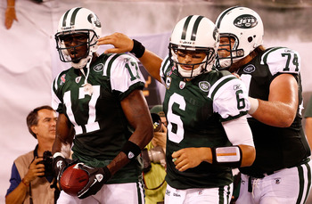 EAST RUTHERFORD, NJ - SEPTEMBER 11:  (L-R) Plaxico Burress #17, Mark Sanchez #6 and Nick Mangold #74 of the New York Jets celebrate after Burress scored a 26-yard touchdown reception in the fourth quarter against the Dallas Cowboys during their NFL Season