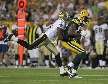 GREEN BAY, WI - SEPTEMBER 08: Tracy Porter #22 of the New Orleans Saints tackles Jermichael Finley #88 of the Green Bay Packers during the NFL opening season game at Lambeau Field on September 8, 2011 in Green Bay, Wisconsin. The Packers defeated the Sain