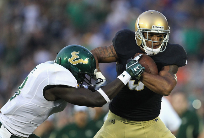SOUTH BEND, IN - SEPTEMBER 03:  Michael Floyd #3 of the Notre Dame Fighting Irish is hit by Jon Lejiste #8 of the University of South Florida Bulls at Notre Dame Stadium on September 3, 2011 in South Bend, Indiana. South Florida defeated Notre Dame 23-20.
