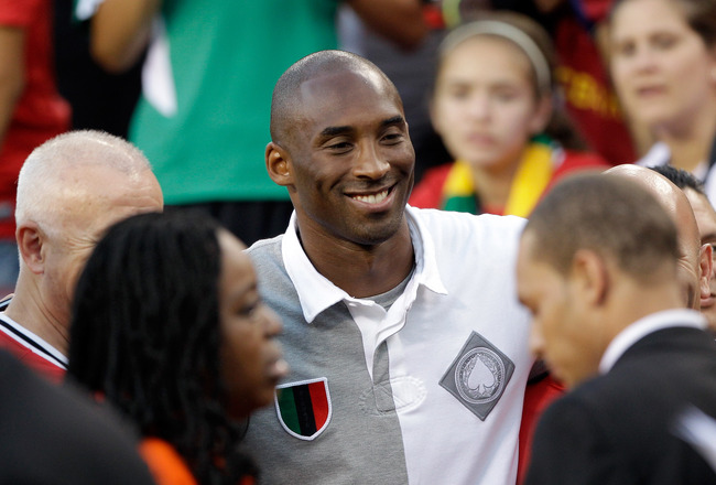 LANDOVER, MD - JULY 30:  NBA basketball player Kobe Bryant poses with fans during a half time event at the Manchester United and Barcelona friendly match at FedExField on July 30, 2011 in Landover, Maryland.  (Photo by Rob Carr/Getty Images)