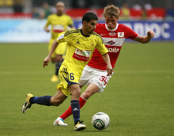MOSCOW, RUSSIA - AUGUST 14: Evgeni Makeev (R) of FC Spartak Moscow battles for the ball with Mbark Boussoufa of FC Anzhi Makhachkala during the Russian Football League Championship match between FC Spartak Moscow and FC Anzhi Makhachkala at the Luzhniki S