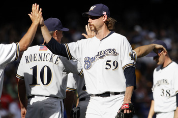 MILWAUKEE, WI - SEPTEMBER 11:  John Axford #59 of the Milwaukee Brewers high fives teammates and coaches after their victory against the Philadelphia Phillies at Miller Park on September 11, 2011 in Milwaukee, Wisconsin.The Brewers beat the Phillies 3-2.