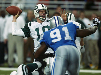 DETROIT, MI - NOVEMBER 17:  Quarterback Chad Pennington #10 of the New York Jets throws a touchdown pass to wide receiver Wayne Chrebet #80 as Robert Porcher #91 of the Detroit Lions gives him pressure during the game at Ford Field on November 17, 2002 in