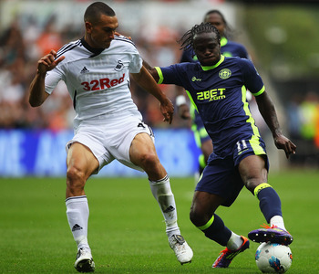 SWANSEA, WALES - AUGUST 20:  Victor Moses of Wigan and Steven Caulker of Swansea challenge for the ball during the Barclays Premier League match between Swansea City and Wigan Athletic at Liberty Stadium on August 20, 2011 in Swansea, Wales.  (Photo by Ma