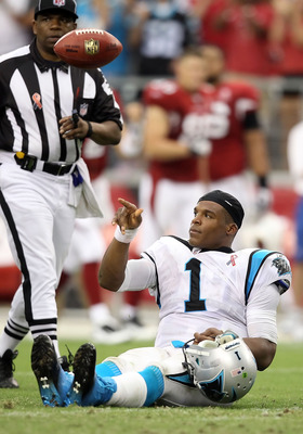 GLENDALE, AZ - SEPTEMBER 11:  Quarterback Cam Newton #1 of the Carolina Panthers flips the football to a referee during the NFL season opening game against the Arizona Cardinals at the University of Phoenix Stadium on September 11, 2011 in Glendale, Arizo