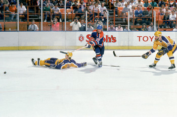 INGLEWOOD, CA - MARCH 1988:  Wayne Gretzky #99 of the Edmonton Oilers makes a pass between defensemen Garry Galley #3 and Jay Wells #24 of the Los Angeles Kings circa March 1988 during a game at the Great Western Forum in Inglewood, California.  (Photo by
