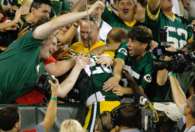 GREEN BAY, WI - AUGUST 19: Alex Green #20 of the Green Bay Packers celebrates a touchdown with a Lambeau leap in the stands against the Arizona Cardinals in a preseason game at Lambeau Field on August 19, 2011 in Green Bay, Wisconsin. (Photo by Scott Boeh