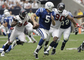 HOUSTON, TX - SEPTEMBER 11: Quarterback Kerry Collins #5 of the Indianapolis Colts is chased down by linebacker Mario Williams #90 and defensive end Antonio Smith #94 of the Houston Texans on September 11, 2011 at Reliant Stadium in Houston, Texas. Texans