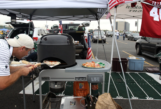 EAST RUTHERFORD, NJ - SEPTEMBER 11:  New York Jets fans Andrew Brucker of Mendham, NJ prepares a pizza as he tailgates outside the stadium prior to the Jets playing against the Dallas Cowboys during their NFL season opening game during their NFL Season Op
