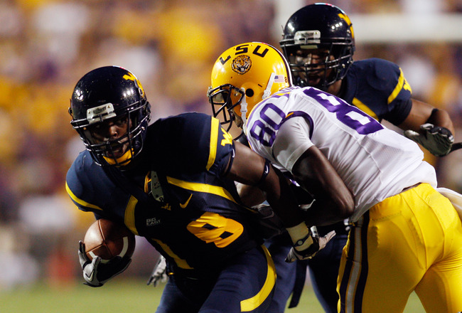 BATON ROUGE, LA - SEPTEMBER 25: Keith Tandy #8  of the West Virginia Mountaineers is tackled after intercepting the ball by Terrence Toliver #80  of the Louisiana State Univeristy Tigers at Tiger Stadium on September 25, 2010 in Baton Rouge, Louisiana.  (