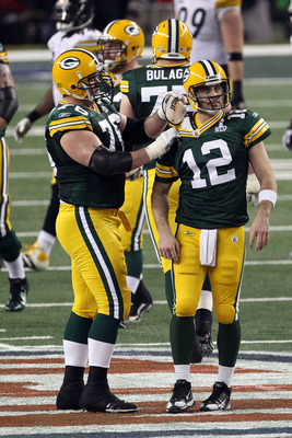ARLINGTON, TX - FEBRUARY 06: Chad Clifton #76 of the Green Bay Packers fixes teammate Aaron Rodgers #12 shoulder pad during Super Bowl XLV against the Pittsburgh Steelers at Cowboys Stadium on February 6, 2011 in Arlington, Texas.  (Photo by Streeter Leck