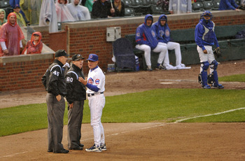 CHICAGO, IL - SEPTEMBER 18:  Manager Mike Quade #8 of the Chicago Cubs (R) argues with umpires Marty Foster (C) and Jeff Nelson after being ejected by Foster during the eighth inning against the Houston Astros at Wrigley Field on September 18, 2011 in Chi