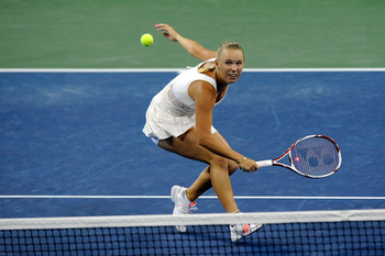 NEW YORK, NY - SEPTEMBER 10:  Caroline Wozniacki of Denmark hits a return against Serena Williams of the United States during Day Thirteen of the 2011 US Open at the USTA Billie Jean King National Tennis Center on September 10, 2011 in the Flushing neighb