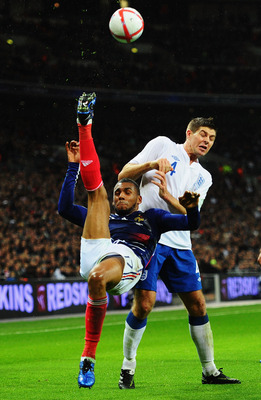 Yann M'Vila battles it out with Steven Gerrard