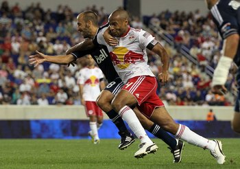 HARRISON, NJ - SEPTEMBER 10:  Thierry Henry #14 of the New York Red Bulls in action against Peter Vagenas #8 of the Vancouver Whitecaps FC at Red Bull Arena on September 10, 2011 in Harrison, New Jersey.  (Photo by Jim McIsaac/Getty Images)