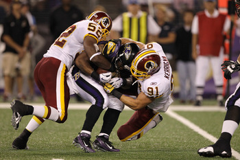BALTIMORE, MD - AUGUST 25: Running back Ray Rice #27 of the Baltimore Ravens is tackled by Rocky McIntosh #52 and Ryan Kerrigan #91 of the Washington Redskins during a preseason game at M&T Bank Stadium on August 25, 2011 in Baltimore, Maryland.  (Photo b