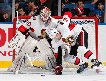 UNIONDALE, NY - JANUARY 13:  Sergei Gonchar #55 of the Ottawa Senators falls down in front of Goalie Robin Lehner #40 of the Senators who protects the net as they were trying to clear the puck out of the crease in the third period of an NHL hockey game ag