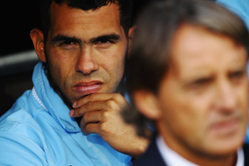 LONDON, ENGLAND - SEPTEMBER 18:  Carlos Tevez (L) of Manchester City sits on the substitutes bench behind his manager Roberto Mancini (R) before the Barclays Premier League match between Fulham and Manchester City at Craven Cottage on September 18, 2011 i