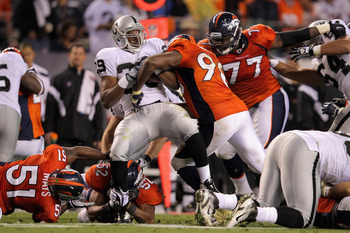 DENVER, CO - SEPTEMBER 12:  Running back  Michael Bush #29 of the Oakland Raiders rushes with the ball as Jason Hunter #90 of the Denver Broncos makes the tackle at Sports Authority Field at Mile High on September 12, 2011 in Denver, Colorado.  (Photo by