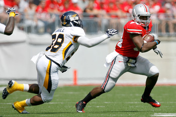 COLUMBUS, OH - SEPTEMBER 10:  Carlos Hyde #34 of the Ohio State Buckeyes is pursued by Robert Bell #38 of the Toledo Rockets on September 10, 2011 at Ohio Stadium in Columbus, Ohio. Ohio State defeated Toledo 27-22. (Photo by Kirk Irwin/Getty Images)