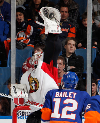 UNIONDALE, NY - JANUARY 13:  Goalie Robin Lehner #40 of the Ottawa Senators reaches high to catch the puck in front of Josh Bailey #12 of the New York Islanders during the third period of an NHL hockey game at the Nassau Coliseum on January 13, 2011 in Un