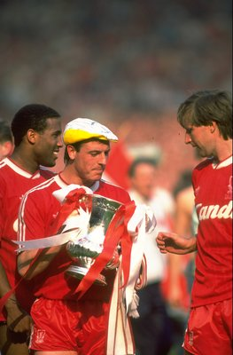 May 1989:  John Barnes (left), Steve McMahon (centre) and Ronnie Whelan (right) all of Liverpool parade on the pitch with the trophy after their victory in the the FA Cup final against Everton at Wembley Stadium in London. Liverpool won the match 3-2. \ M