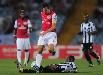 UDINE, ITALY - AUGUST 24:  Robin van Persie of Arsenal battles with Emmanuel Agyemang-Badu of Udinese during the UEFA Champions League play-off second leg match between Udinese Calcio and Arsenal FC at the Stadio Friuli on August 24, 2011 in Udine, Italy.