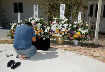 RANCHO PALOS VERDES, CA - JULY 28:  Ichiro Sakashita prays next to flower bouquets left on behalf of the Japanese Hanshin Tigers baseball team, outside the home where former Major League Baseball pitcher Hideki Irabu was found dead yesterday after an appa